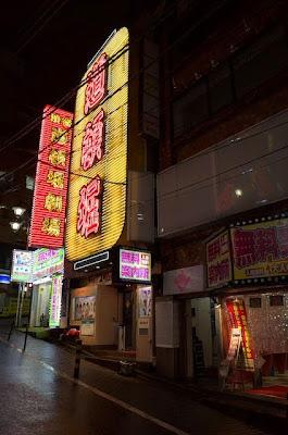 お店の前の百軒店通りのネオン街