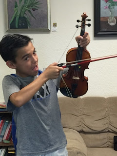 student uses violin and bow to shoot like an arrow