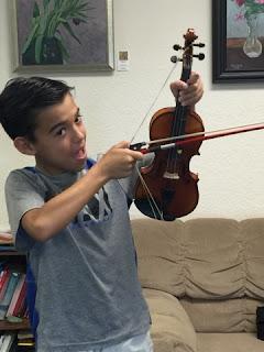student uses violin and bow to shoot like an arrow