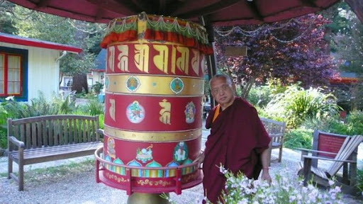 Lama Zopa Rinpoche and a prayer wheel at Land of Medicine Buddha.
