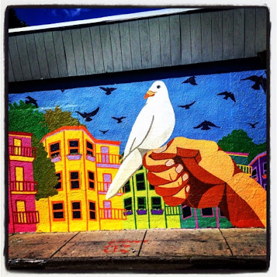 "Murals of Boston: ""A Bird in the Hand Is Worth Two in the Bush"" featuring a Dove and Classic Boston Triple Deckers, as seen in Roslindale, near Forest Hills"