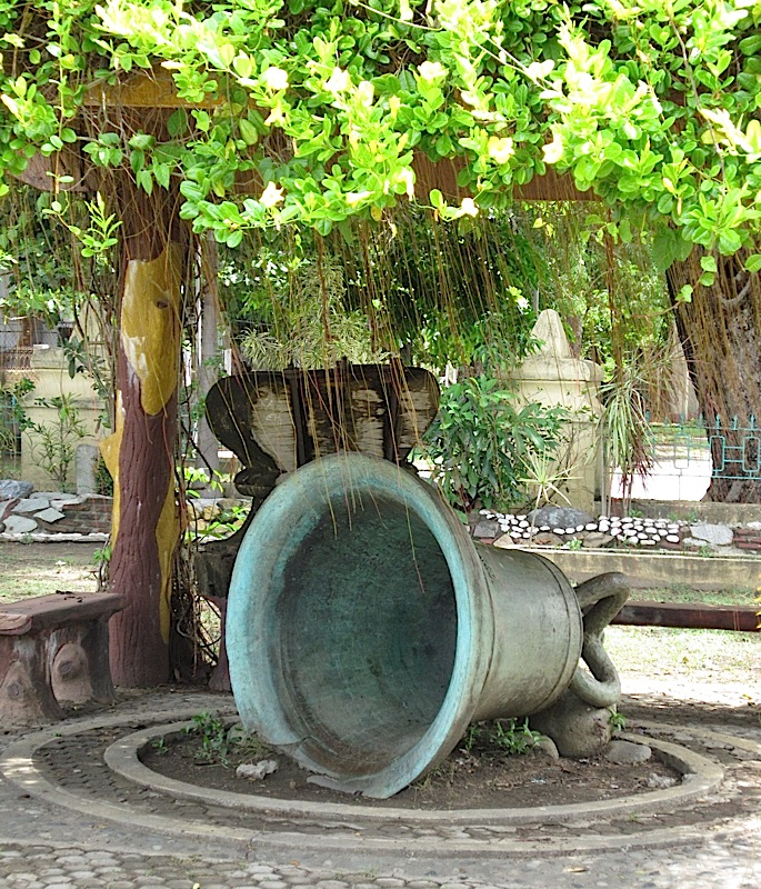 old bronze church bell in the garden of St. Michael the Archangel Catholic Church in Bacnotan