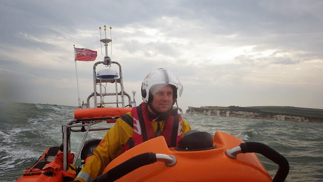 Dave Riley at the helm as the ILB tows a yacht towards Poole Harbour - 28 September 2013. Photo credit: RNLI / Rob Inett