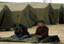 Egyptian refugees fleeing violence in Libya sit in a refugee camp after crossing into Tunisia near the border crossing of Ras Jdir February 25, 2011. Hundreds of Egyptian refugees were transported from a border refugee camp to another location inland. At