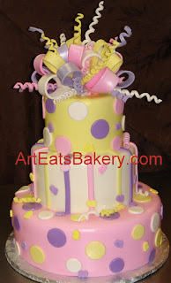 Three tier custom baby shower cake with yellow, pink and purple bow, stripes, polka dots, and baby feet