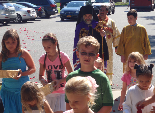 The children throw rose petals along the path before the Bishop.