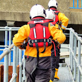 Poole ILB crew getting kitted on their way to the lifeboat to launch to a 4m Thames launch with mechanical problems 21 August 2014 Photo: Anne-Marie Clark