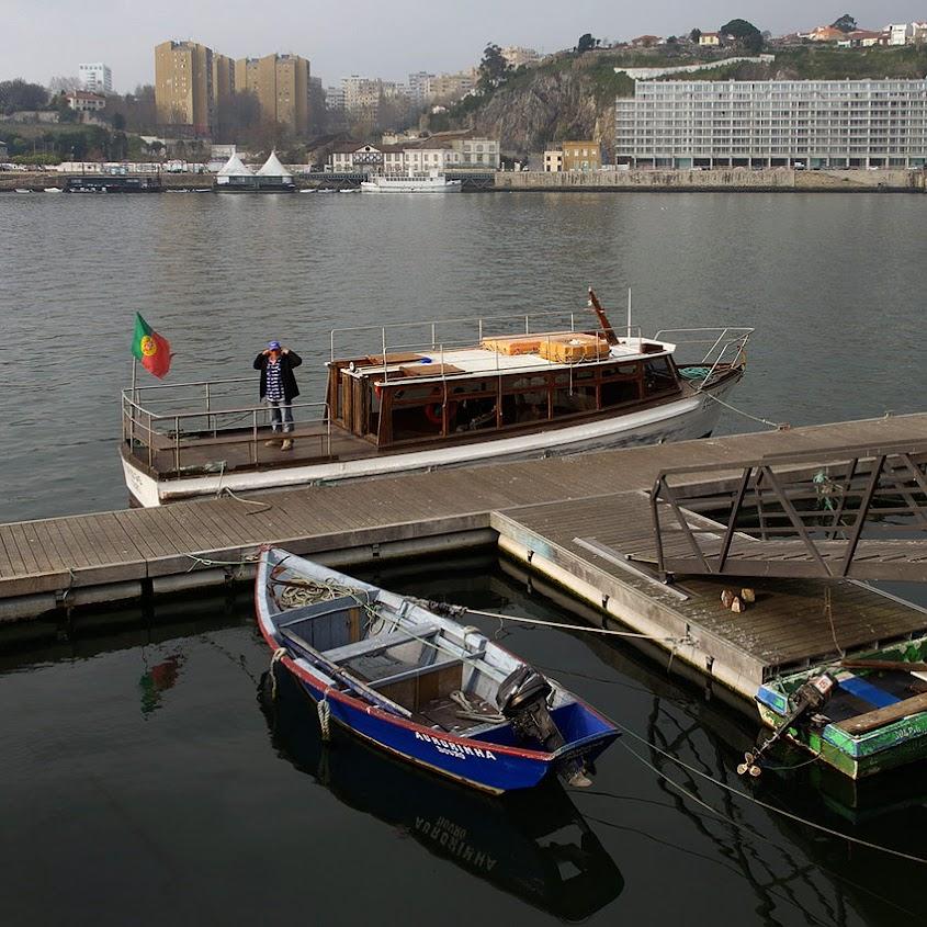 Cais de embarque com um pequeno barco de pesca e a traineira de transposte entre margens.