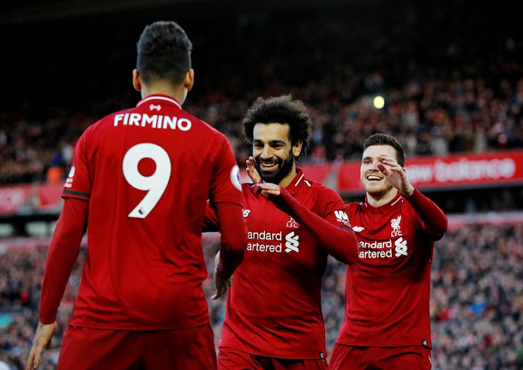 Liverpool's Mohamed Salah celebrates scoring their third goal with Roberto Firmino and Andrew Robertson. Liverpool beat Bournemouth 3-0 at Anfield on Saturday.