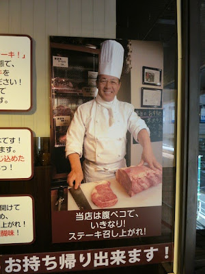 店頭に貼られたお肉をガッツリ切るコックの写真