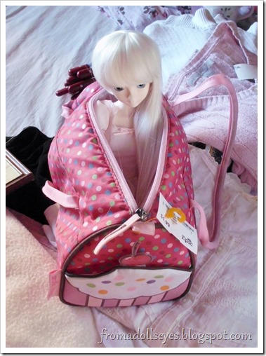 A ball jointed doll checking the size of a cute bag, by climbing inside it.