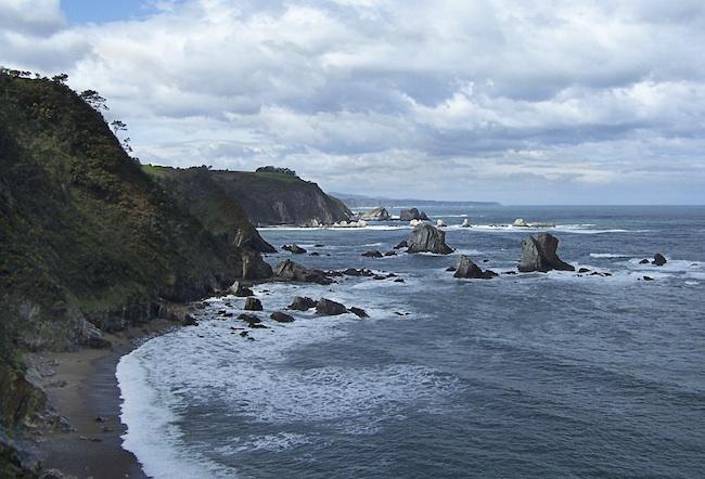 Playa rocosa al pie de un acantilado un dia niblado