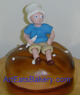 Baker sugar figure with rolling pin sitting on top of a custom unique fondant round loaf of bread birthday cake design