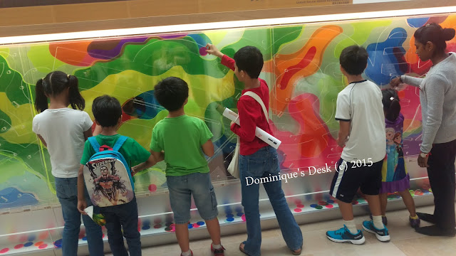 The kids putting color discs inside a wall