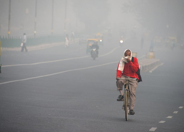 An Indian man rides a bike amid heavy smog on a street of New Delhi on 10 November 2017. Photo: Dominique Faget / AFP / Getty Images