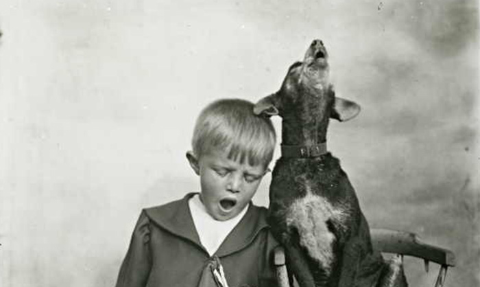 Small (Australian) boy with a pet dog singing in (peaceful) unison (1939).