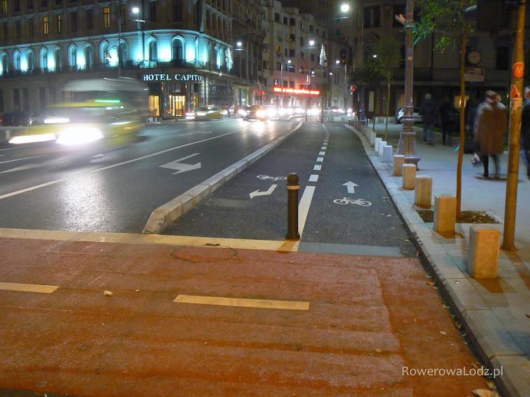 Dwukierunkowa droga dla rowerów - dla zjeżdżających pas do skrętu i dalej przejazd wymalowany na czerwono.