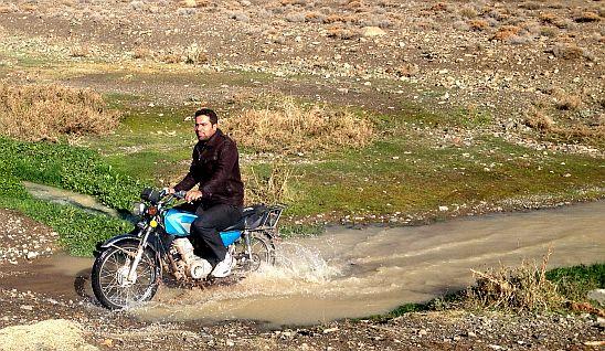 Motorradfahrer fährt durch Bach bei Abyaneh