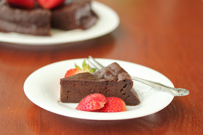 photo of a slice of chocolate cake on a plate with sliced strawberries