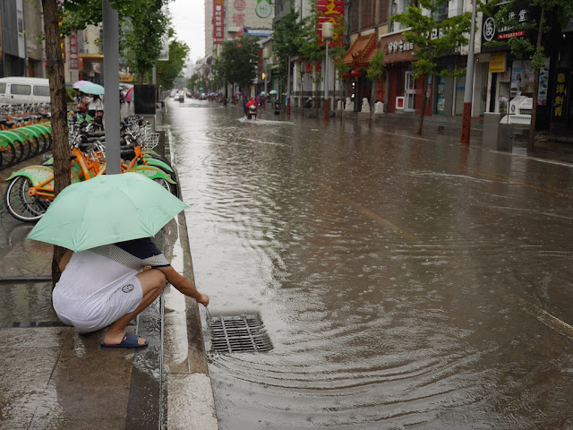young man clearing debris from a grating for drainage on a flooded street in Taiyuan, China