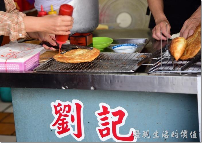 台南安平-劉記韭菜盒。店家會幫客人在烙餅上先淋上甜辣醬,不想要的可以是先講,工作熊個人建議一定要加甜辣醬,可以增加美味度。