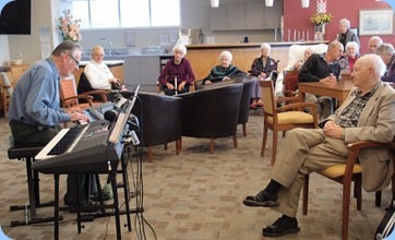 Roy Steen playing his Korg Pa300 to great effect and intently watch-on by residents. Photo courtesy of Dennis Lyons.
