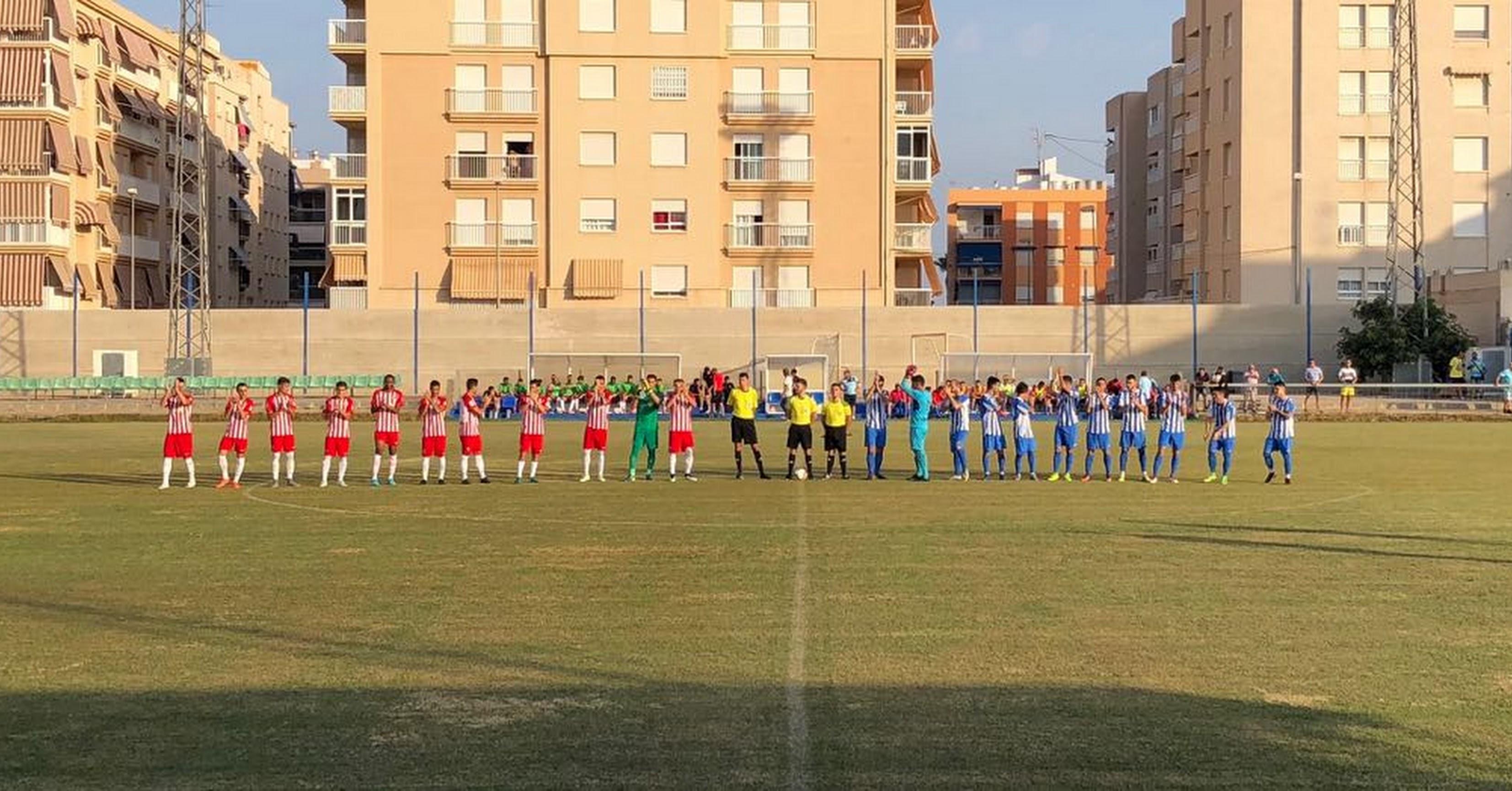 Los equipos se saludan en el centro del campo.