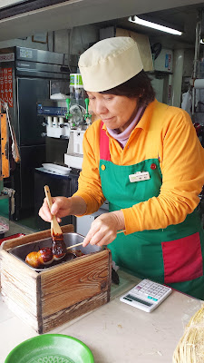Brushing the sauce on dango, a chewy Japanese dumpling and sweet made from mochiko (rice flour) that are usually serve skewered at a Mount Takao stand