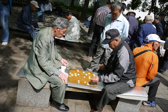 two men playing janggi (Korean Chess) at a park in Seoul