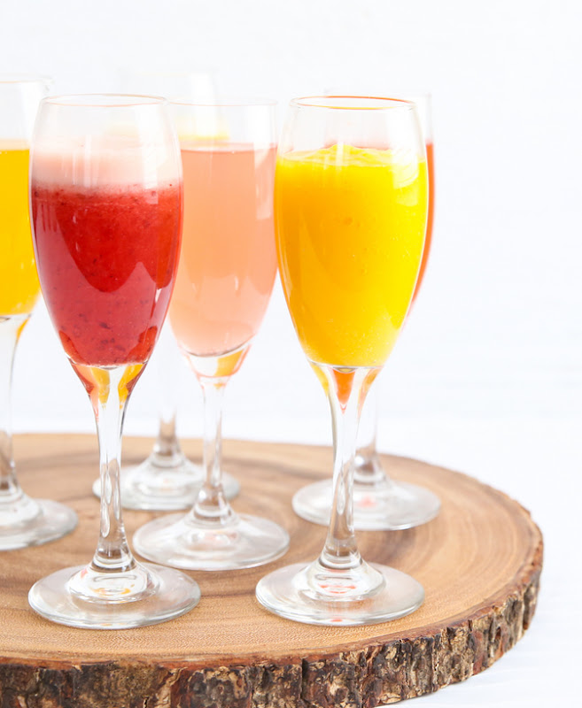 photo of different flavored non-alcholic mimosas on a wooden board