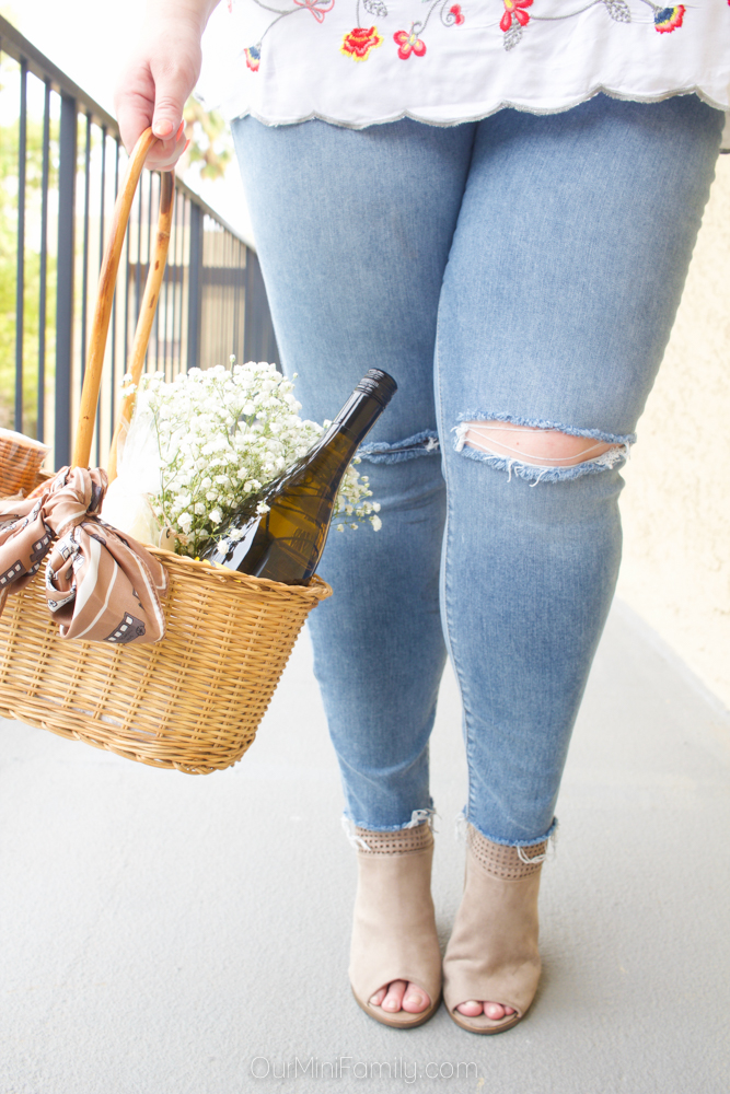 woman wearing distressed skinny jeans holding a gift basket with wine