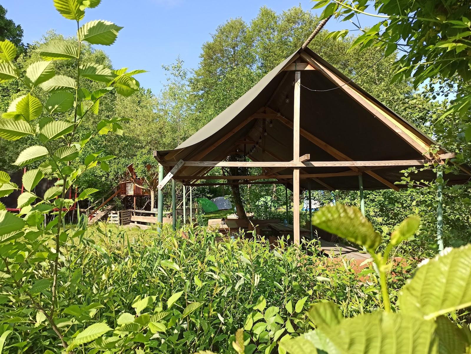 zadaszenie a w tle namioty, których mieszkańcy jeszcze śpią. pole namiotowe.
