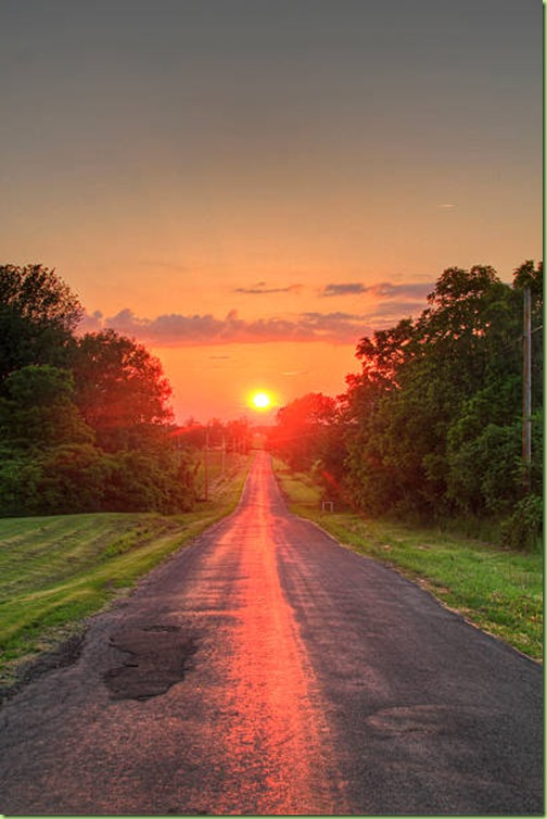 A beautiful summer sunset exactly at the end of a long straight country road