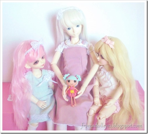 A msd sized ball jointed doll holding a lalaloopsy doll while two smaller yosd sized ball jointed dolls are looking at it and asking to play with it.
