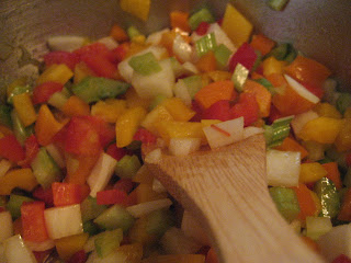 Sauteed peppers, onions, and celery in a pan with a wooden spoon.