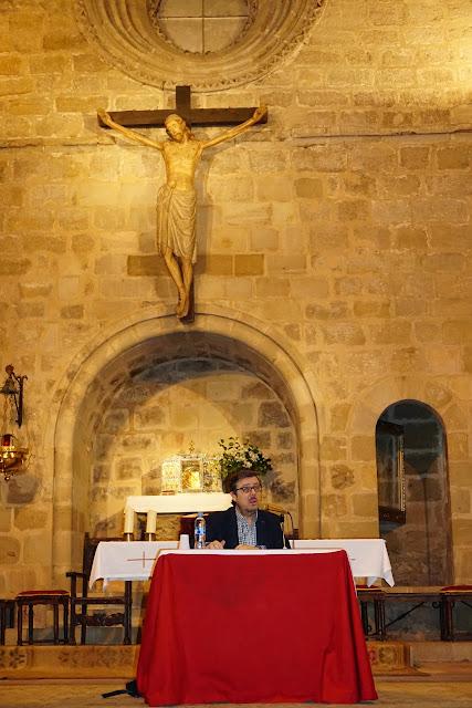 El conferenciante aparece sentado en el presbiterio, frente al altar, con el gran crucificado gótico de fondo