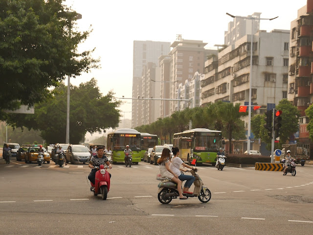 two females on a scooter with a PRC flag in Zhongshan, China