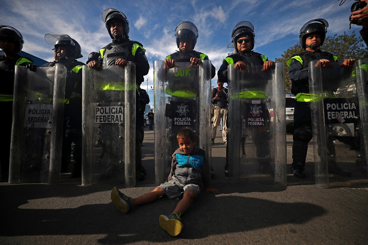 A migrant boy from Honduras in front of Mexican riot police.