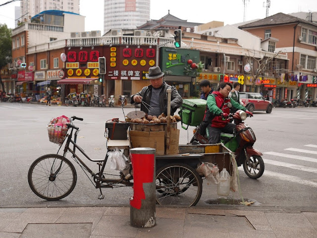 man wearing hat selling sweet potatoes from a tricycle cart at intersection of Shaanxi North Road and Xinhui Road