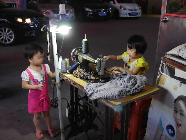 two kids at a sewing machine outside at night
