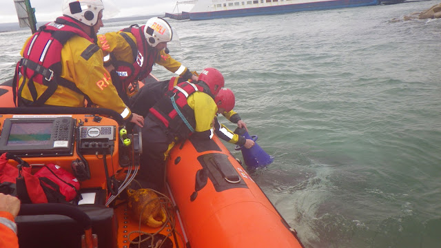 Volunteer RNLI crew members assist the firemen to inspect the submerged vehicle off North Haven - 27 October 2014.  Photo credit: RNLI/Poole