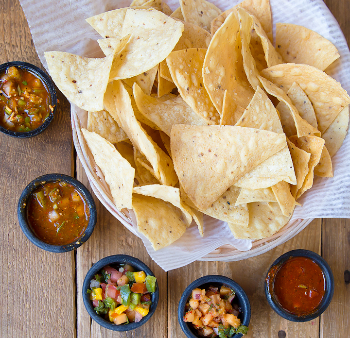 overhead photo of a basket of chips and different kinds of salsa