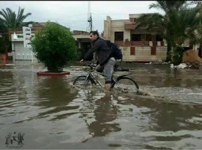 sepeda melewati banjir besar yang membenamkan lingkungan
