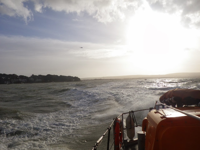 The ALB returns to harbour, while the coastguard helicopter is in the sky over Poole Bay. 7 January 2014.  Photo credit: Anne Millman, RNLI Poole.