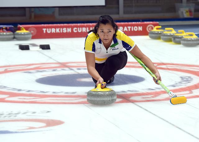 Anne Shibuya lança uma pedra amarela em jogo do Pré-Olímpico de Curling