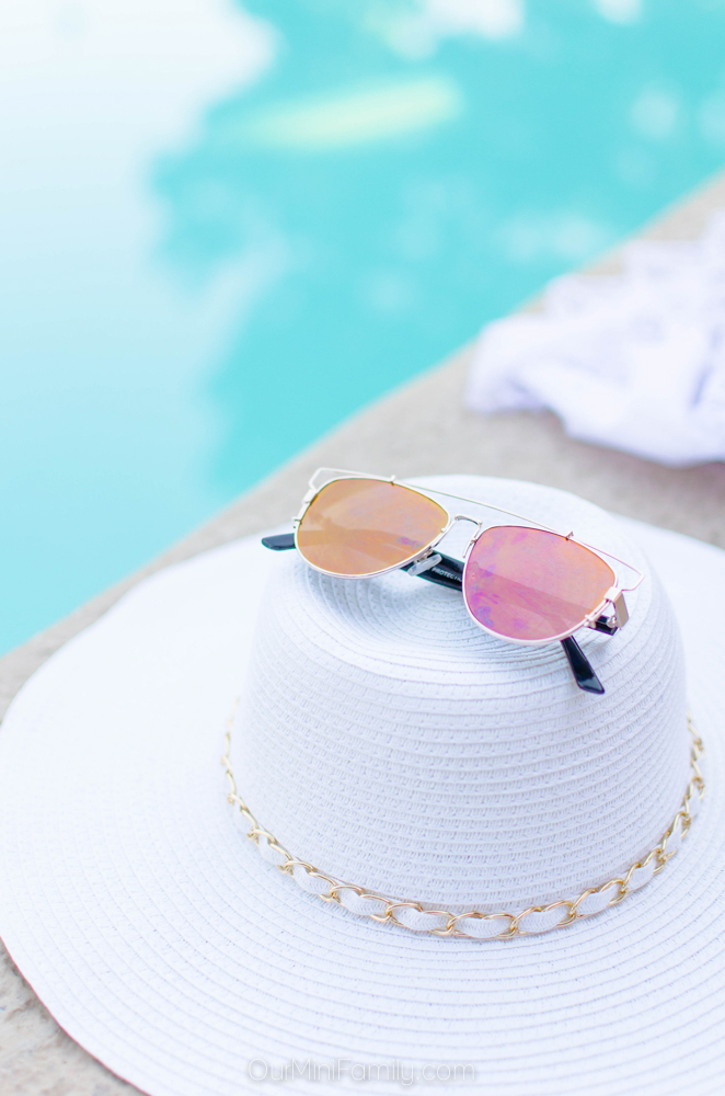 tinted mirror sunglasses balancing on top of a white sunhat