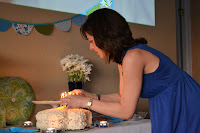 A guest lights the candles on the daisy birthday cake.