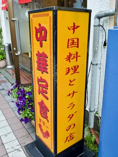 中国料理とサラダの店、中華定食天下一、と書かれた黄色い立看板