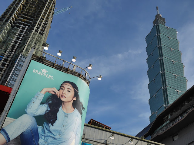 view from Xinyi shopping district of Taipei 101, and under-construction building, and an ad for Brappers