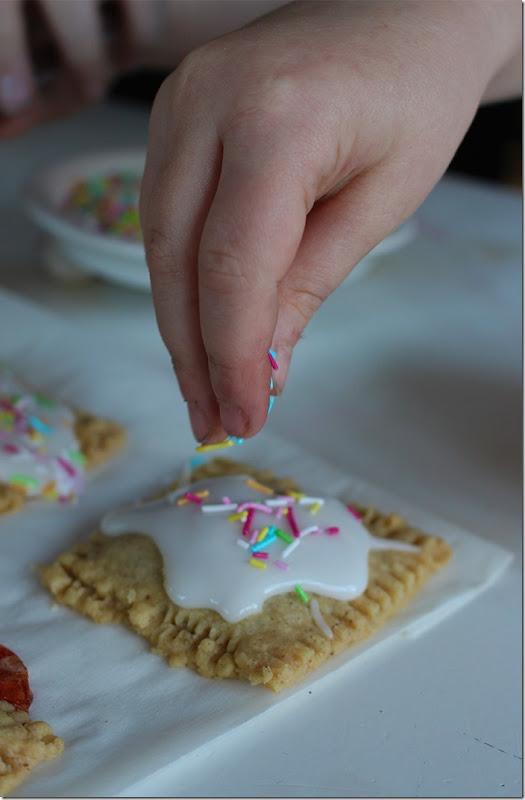Närbild på barnhand som strör strössel på en glaserad mördegskaka